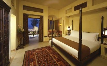 Bab Al Shams Desert Resort and Spa Dubai bedroom with corner sofa and access to patio
