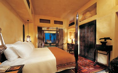 Bab Al Shams Desert Resort and Spa Dubai bedroom with carved furniture and access to terrace