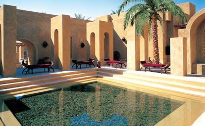 Bab Al Shams Desert Resort and Spa Dubai courtyard pool with red loungers