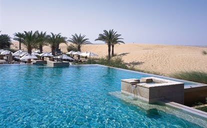 Bab Al Shams Desert Resort and Spa Dubai desert pool with umbrellas and palm trees