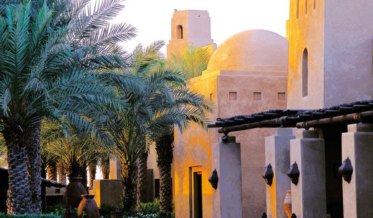 Bab Al Shams Desert Resort and Spa Dubai exterior architecture stone building with domed roof and palm trees
