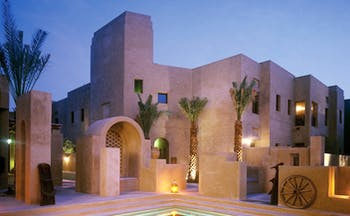 Bab Al Shams Desert Resort and Spa Dubai exterior night stone architecture with pool and wheel