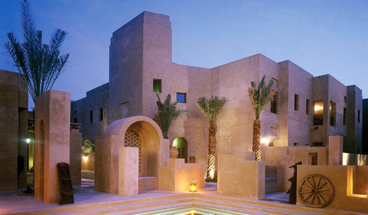 Bab Al Shams Desert Resort and Spa Dubai exterior night stone architecture with pool and wheel