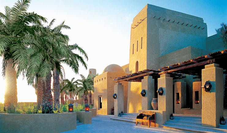 Bab Al Shams Desert Resort and Spa Dubai exterior traditional Arabic building with palm trees and lanterns
