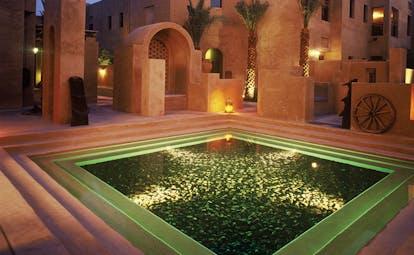 Bab Al Shams Desert Resort and Spa Dubai fountain night square pool in courtyard at night