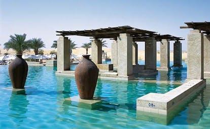 Bab Al Shams Desert Resort and Spa Dubai pool with covered area and urns
