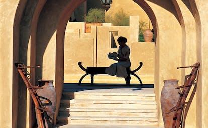 Bab Al Shams Desert Resort and Spa Dubai terrace woman reading a book in a courtyard