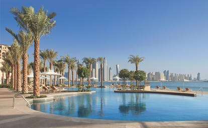 Fairmont the Palm Dubai outdoor pool palm trees and skyscrapers
