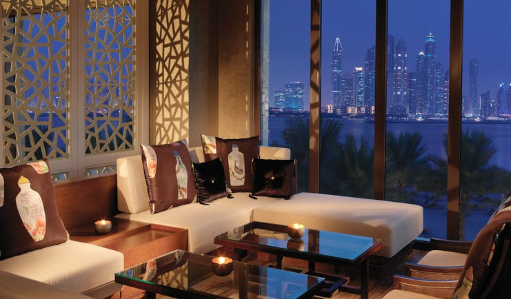 Fairmont the Palm Dubai restaurant with large windows and city view at night