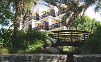 Palm Tree Court Jebel Ali Dubai exterior building with balconies overlooking garden with bridge