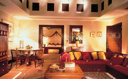 The Jumeirah Beach Hotel Dubai villa lounge with large sofa and table with view of bedroom