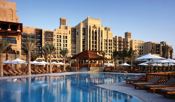 Madinat Jumeirah Dubai hotel pool view overlooking swimming pool with loungers and umbrellas