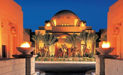One and Only Royal Mirage Dubai courtyard with torches overlooked by building with domed roof