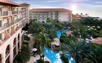 The Ritz-Carlton Dubai exterior view of hotel with balconies pools and palm trees
