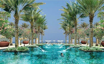 Al Bustan Palace Hotel Oman outdoor pool with palm trees and flowers