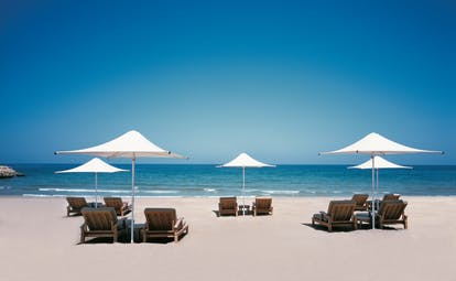 Shangri La Barr Al Jissah Resort and Spa Oman beach with loungers and umbrellas