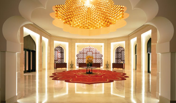 Hall area with white column pillars, a red rug and intricately detailed ceiling