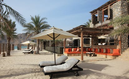 Six Senses Zighy Bay Oman beach lounge terrace private beach area with loungers and umbrellas
