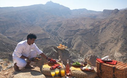 Six Senses Zighy Bay Oman mountain picnic waiter setting up a picnic in the mountains