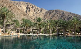 Six Senses Zighy Bay Oman outdoor pool overlooked by mountains with covered loungers