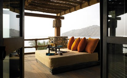 Six Senses Zighy Bay Oman retreat terrace lounge bed on balcony with drink and view of sea and mountain