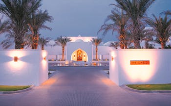 The Chedi Muscat Oman exterior white building complex with palm trees
