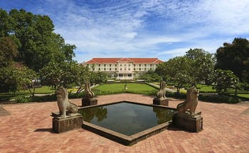 Raffles D'Angkor exterior, hotel building, grand architecture, patio with ornate water feature, lawns, trees