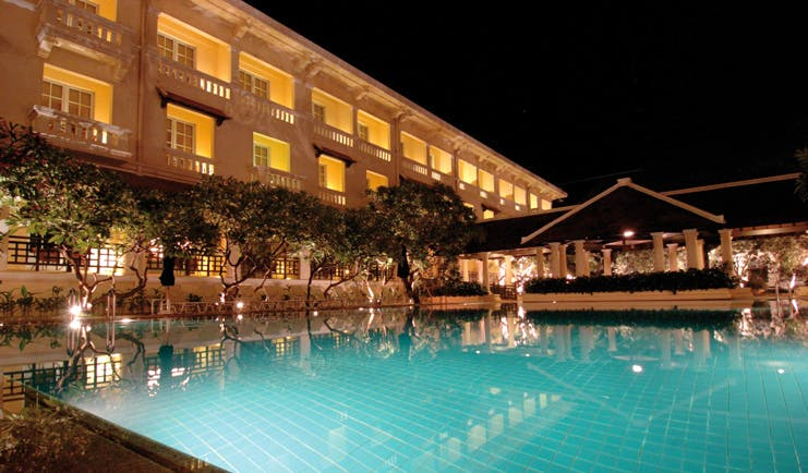 Raffles Hotel Le Royal Cambodia exterior night swimming pool trees romantic lighting