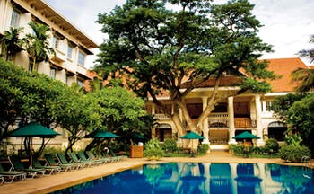 Raffles Hotel Le Royal Cambodia exterior pool loungers trees hotel building