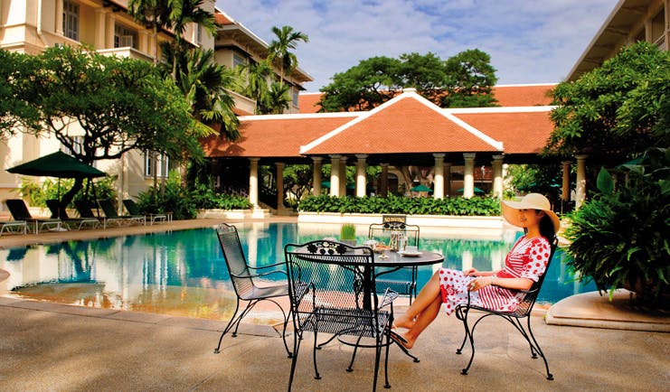Raffles Hotel Le Royal Cambodia outdoor swimming pool courtyard loungers umbrellas seating area