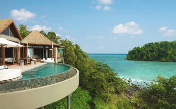 Overview of the Song Saa Private island showing beach hut style buildings with an infinity pool looking over the ocean