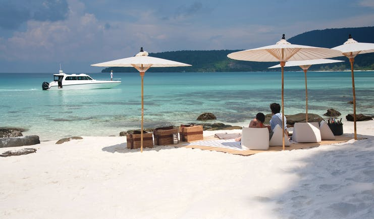 Picnic of the neighbouring island of Koh Rong with white sandy beaches leading onto a clear turqouise sea with white umbrellas and wooden picnic baskets on the sand