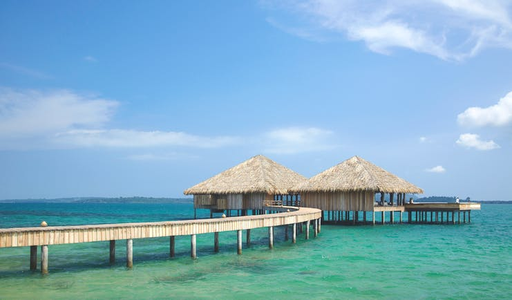 View of a restaurant at Songa Saa Private island with two beach huts on top of the sea with a bridge leading to them