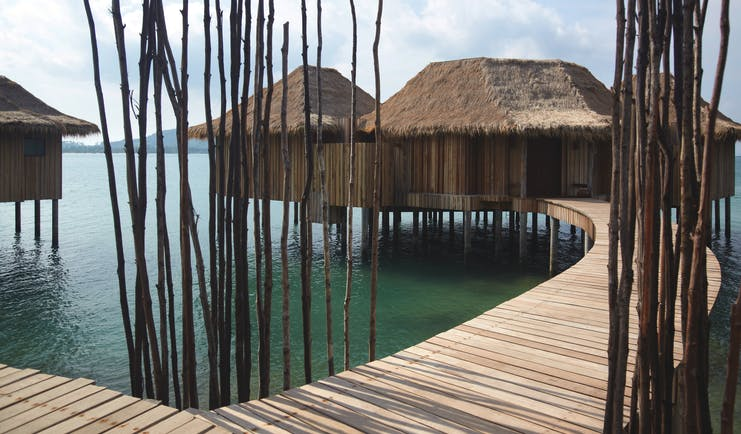 Exterior of the two bedroom overwater villas with beach hut style roof and wooden bridge over the sea to enter