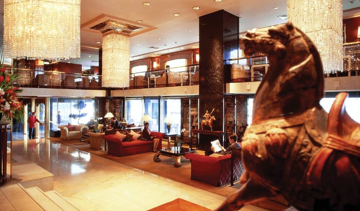 Mandarin Oriental lobby with horse statue, large chandeliers and high ceilings