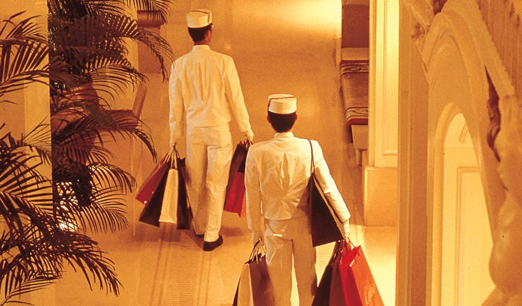 The Peninsula Hong Kong hotel service uniformed staff members carrying shopping bags