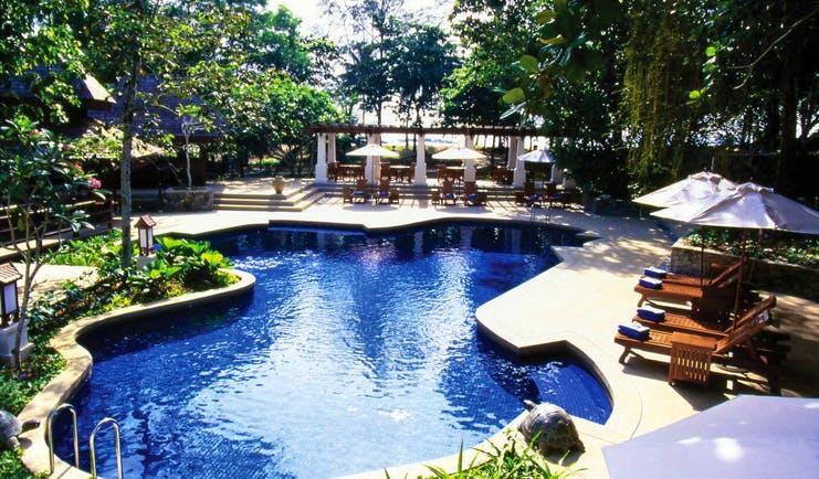 Tanjong Jara Malaysia pool sun loungers umbrellas greenery trees