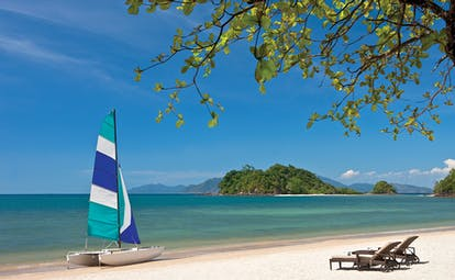 Andaman Langkawi white sandy beach with loungers and sailboat with blue and white sail, islands in distance