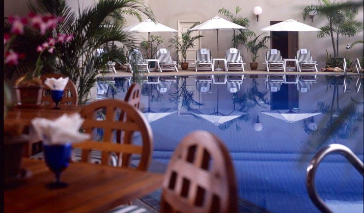 Ritz Carlton Kuala Lumpur pool sun loungers umbrellas poolside dining area