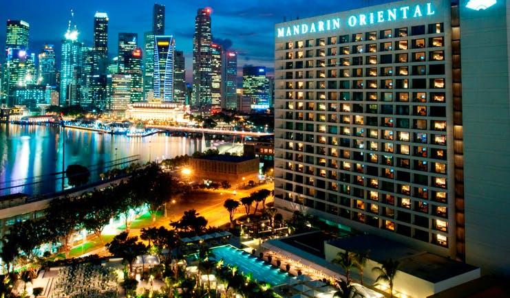 Mandarin Oriental Singapore exterior at night hotel building overlooking harbour city landscape