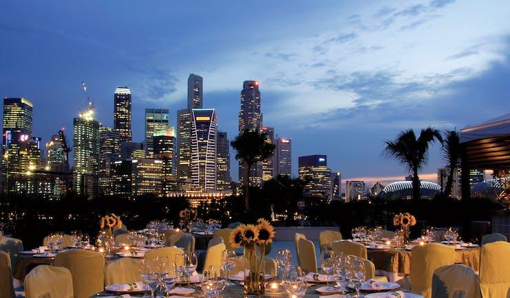Mandarin Oriental Singapore terrace outdoor dining overlooking harbour city in background