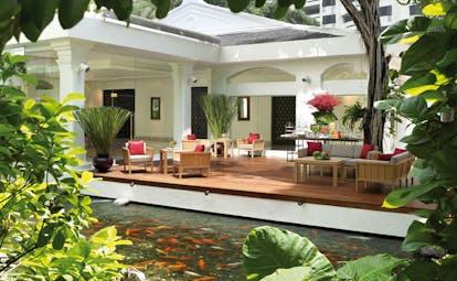 Anantara Siam Bangkok Thailand koi pond white building decked seating area garden