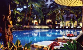 Anantara Siam Bangkok Thailand outdoor swimming pool loungers umbrellas garden pond night time