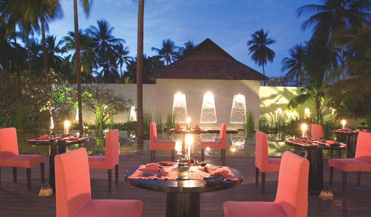 Evason Hua Hin Resort Thailand The Other Restaurant outdoor dining pink chairs pond palms trees night time