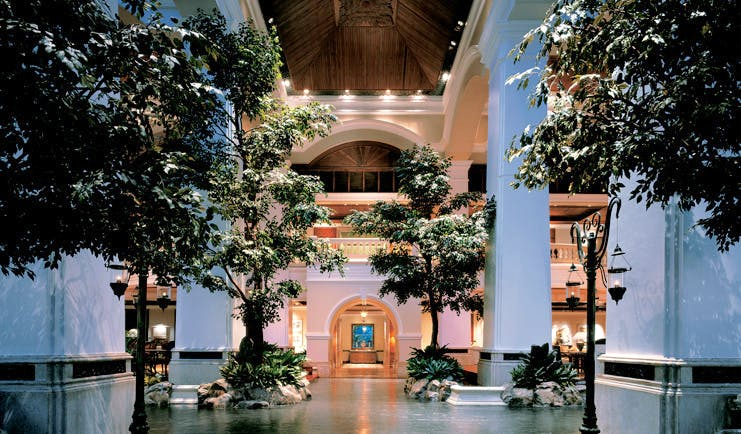 Grand Hyatt Erawan Bangkok Thailand atrium lobby trees columns night time