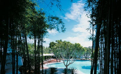 Grand Hyatt Erawan Bangkok Thailand Isawan pool outdoor pool loungers umbrellas trees
