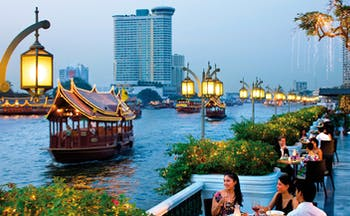 Mandarin Oriental Bangkok Thailand riverside terrace dining view of river traditional thai boats