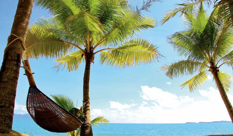 Santiburi Resort Thailand hammock tied between two palm trees on the beach