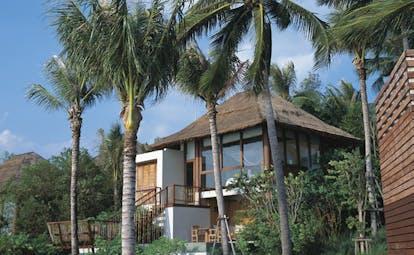Six Senses Samui Thailand pool villa exterior thatched roofed villa palm trees