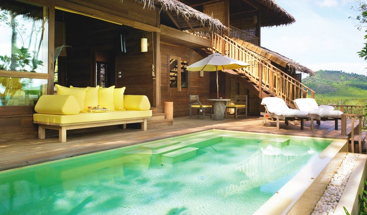 Exterior view of a deluxe villa at the Six Senses Yao Nai with a large rectangular pool with wooden decking area, seating areas with beach hut style buildings to the side